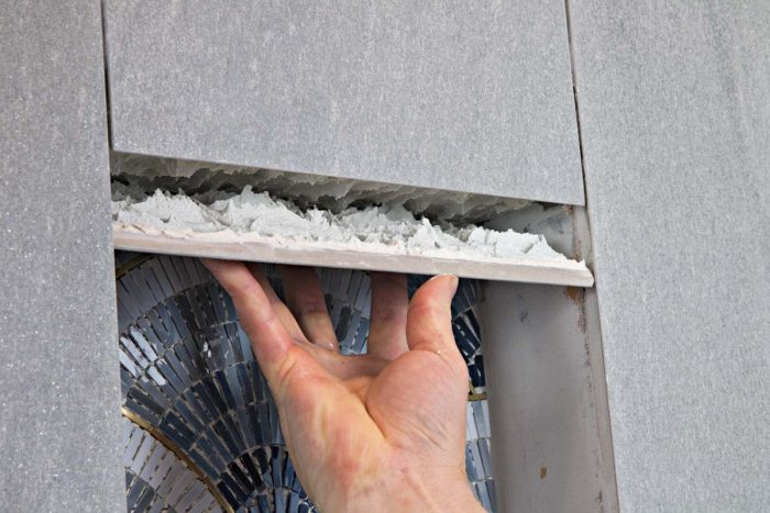Again, the front edge is mitered where it meets the wall tile. As with the sides and bottom of the niche, add as much thinset as it takes to position this tile square to the others while leaving a thin, even gap.