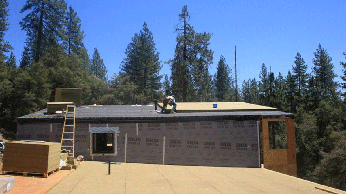 The insulation planes with the roof overhang on the left. An underlayment will be installed over the insulation and overhang and then the metal roof is installed directly on top of the underlayment.