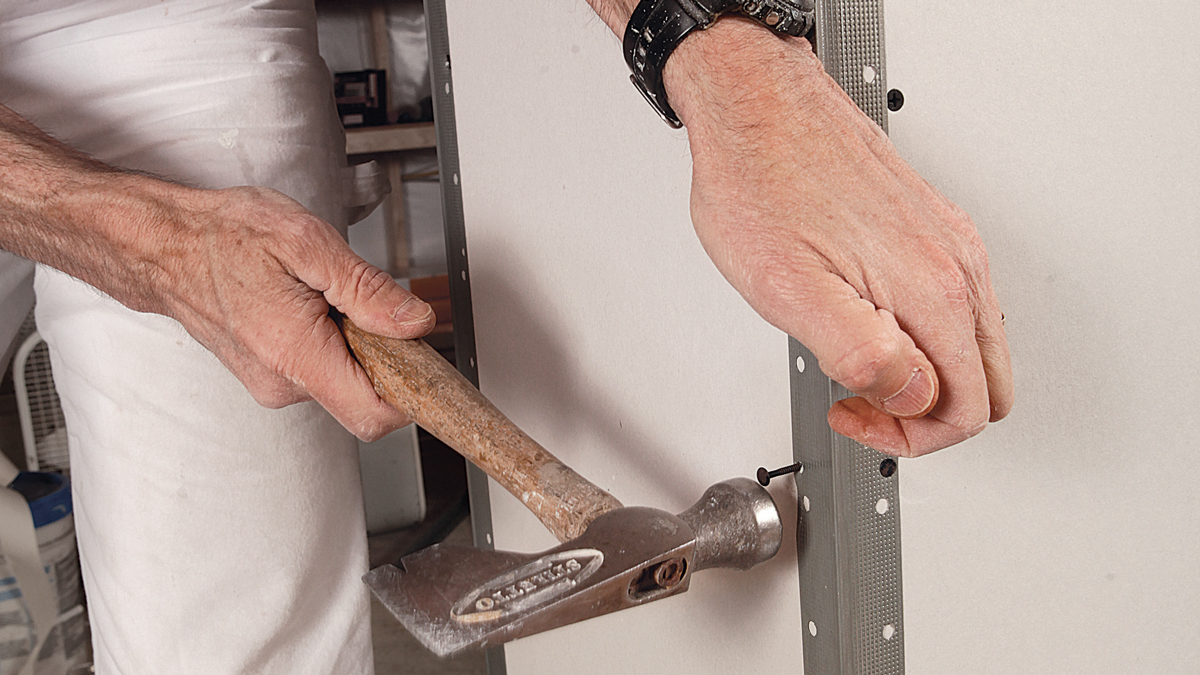 Don't stagger. Fasten every 8 in. along the flanges through the small holes—I prefer drywall nails over screws for this—and always put the fasteners in opposition, not staggered. Staggering can cause the edge on the other side to pucker out.