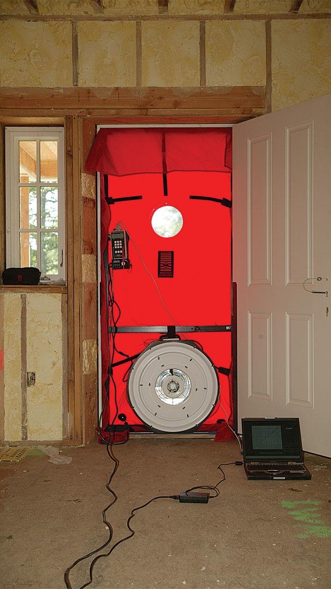House with a blower door in the doorway is shown
