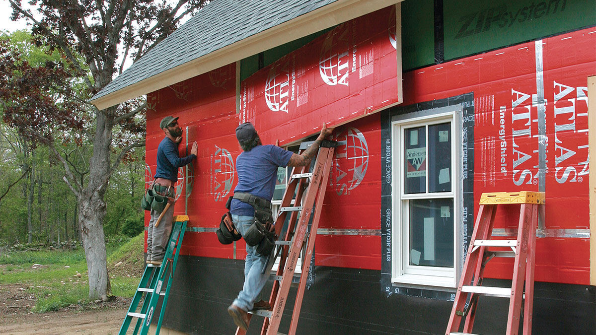 two people working on the exterior of a house