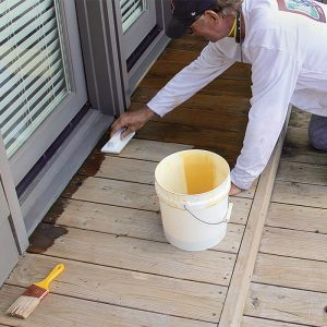 Cut in. Use a brush or painting pad to cut in along the house and anywhere else at risk of overspray from the airless sprayer used for the rest of the deck. I prefer a pad because it holds more finish than a brush.