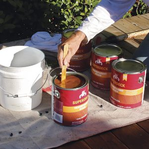 Stir and mix the stain. Stir the cans of stain individually and then mix the cans together in a bucket to ensure even coloring throughout the deck surface.
