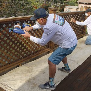 Start at the top. Vertical surfaces and anything above the deck get coated before moving to the deck surface. A small airless sprayer is great for coating railings, but once the coating is sprayed, work it into the surface and absorb any excess with a painting pad.
