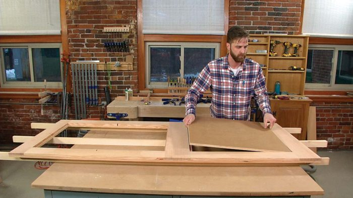 Fit the panel. Drop the 5⁄8-in.-thick MDO panel—a type of waterproof plywood—into the middle layer, where it will be captured by the interior and exterior layers.