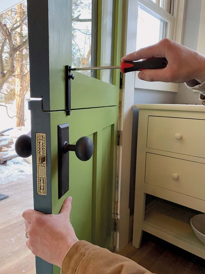 Add the hardware. After painting the door, slide the mortise lock into place, add a deadbolt if desired, and install a slide bolt to connect the two halves of the door.
