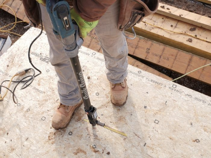 Another carpenter follows behind with collated screw gun. The Simpson StrongTie Quick Drive system is fast and ergonomic.