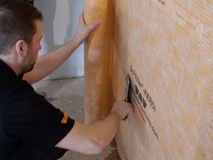 As the Kerdi is embedded in the thinset, a drywall knife ensures adhesion and squeezes out excess thinset.