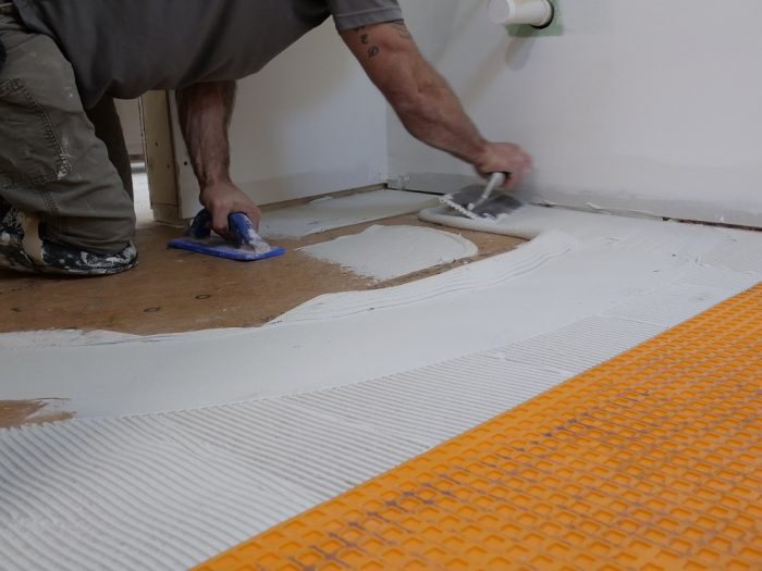 The Schluter-Ditra is installed over the AdvanTech subfloor outside the shower area.