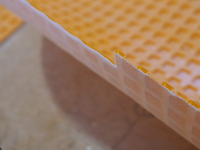The hollow plastic grid on the upper surface of the Ditra allows the tile to move horizontally