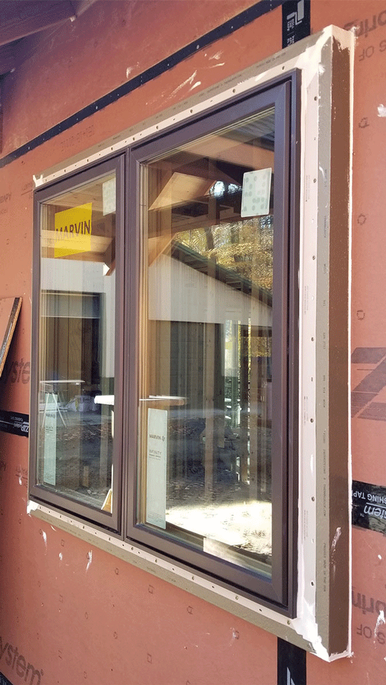In addition to the continuous exterior insulation of R-8 ComfortBoard, the walls were insulated with R-21 fiberglass batts, and ThermalBuck was installed at the openings to allow windows to be in the same plane with the siding after 2 in. of ComfortBoard 80 was installed.