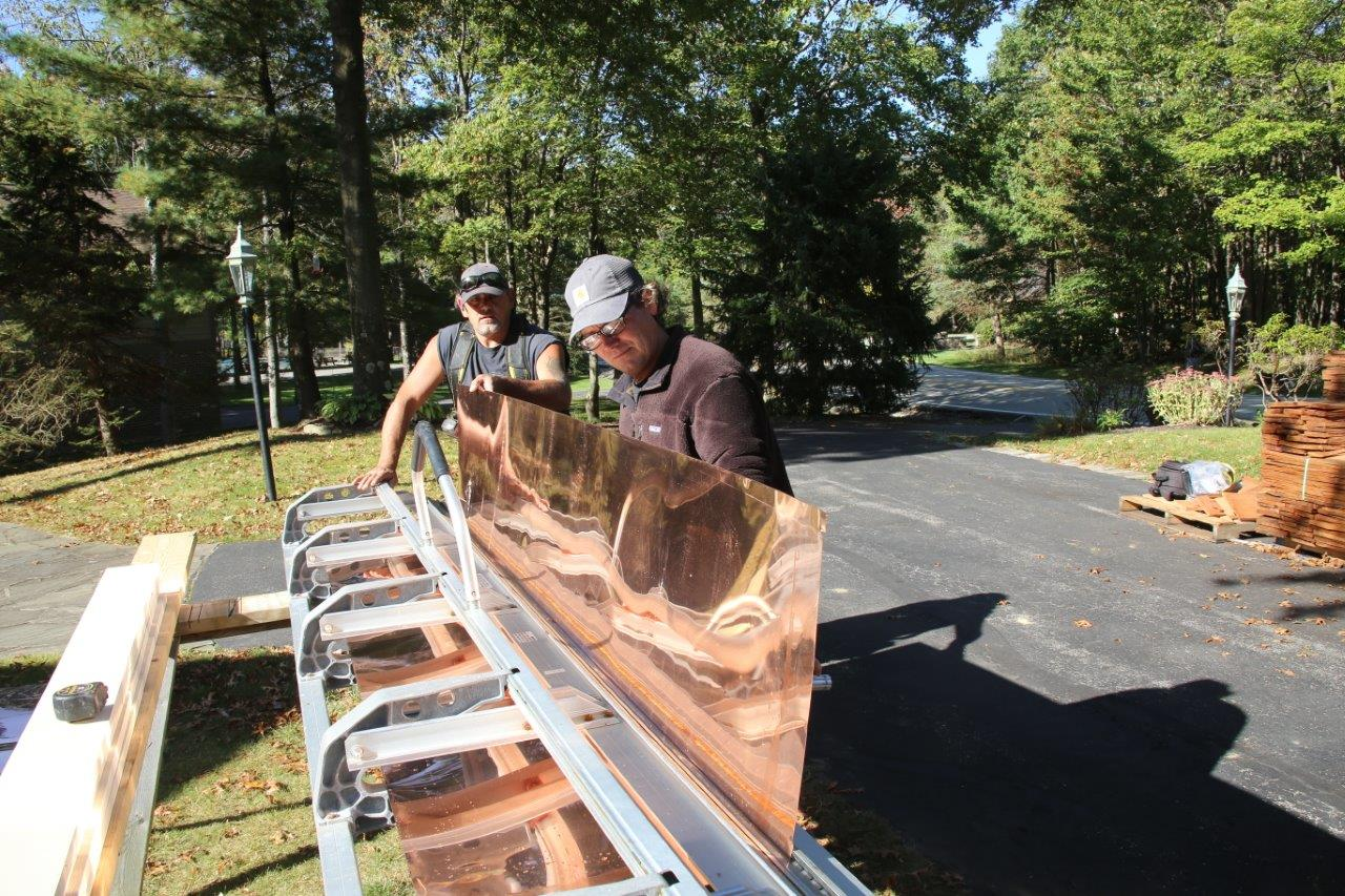 Two people work on bending a large sheet of copper