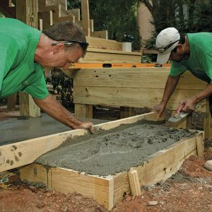 A level form is critical. A concrete pad is formed to terminate the two-tread run from the landing above. After setting and filling the form, screed the concrete flush with the top of the form, and trowel it smooth.
