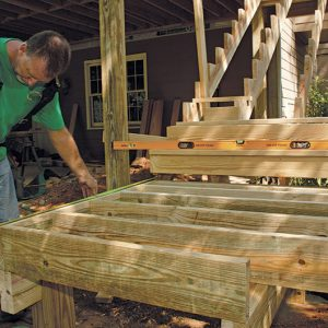 Build the landing in place. With a pair of carrying beams in place, the landing box can be framed. Note the clipped corner detail and 12-in.-on-center framing. Like the deck above, the landings are decked with a diagonal pattern.