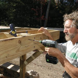Tie the joists together with blocks. Spaced with a scrap of post material, screw two blocks of joist material between the outer pair of joists using 6-in. FlatLoks.