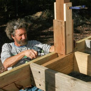 Screw the post to the rim joist. A pair of 8-in. ThruLoks tie the rim, post, and blocking together.