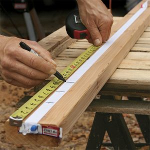 Mark the template. With one end pinned, stretch the elastic about 1 ft. longer than the longest rail. Relax it about 10 in., and pin the other end. Snap it a couple of times to equalize the stretch, then mark the ends of the longest rail and the baluster spacing.