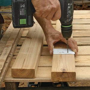 Use a template made from aluminum coil stock to drill the rail sections. The two holes in the template are half the baluster thickness in from the edge. Align the template edge with the baluster-edge marks on the rails to center the holes in the balusters.