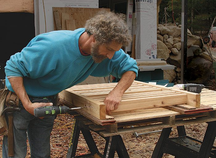 Assembly bench doubles as a jig. Spaced 24 in. apart, strips of 1⁄2-in. plywood raise the 2-1⁄2-in.-deep balusters 1⁄2 in. off the bench, aligning them perfectly on the 2x4 rails. Two 2-1⁄2-in. stainless-steel trim-head screws hold each baluster to each rail.