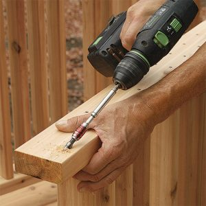 Drill the rails for toe-screws. The rails are screwed to the 4x4 posts from the bottom to hide the 2-1⁄2-in. stainless-steel screws. Drill the pilot holes at about a 60° angle through the bottom ends of the rails.