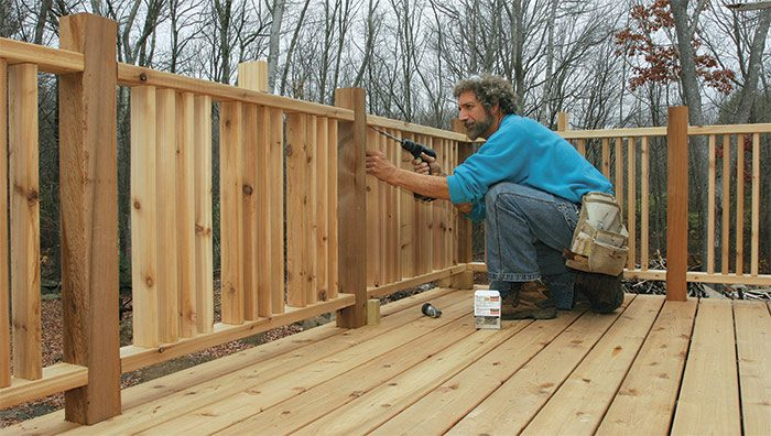 Fasten the top first. Spacer blocks hold the railing the correct height off the decking. A long extension helps to set the screws without the spinning driver marring the balusters.