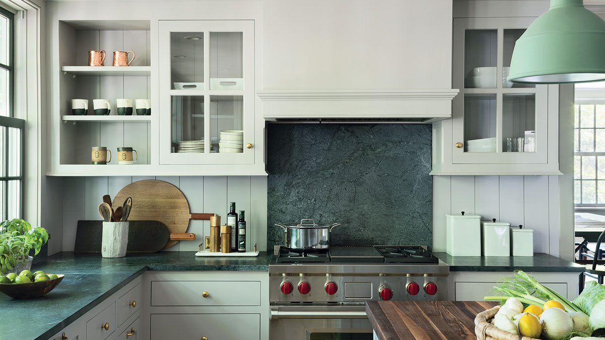 a kitchen with traditional white cabiners, open window doors, and dark counters