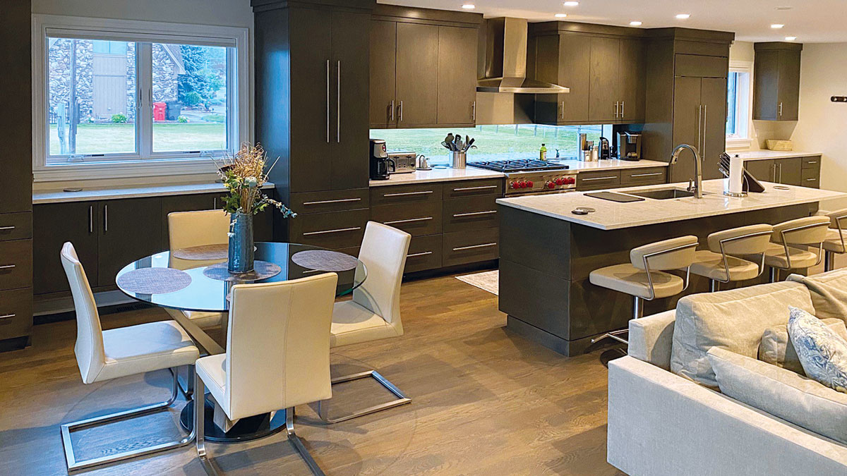 a view of the kitchen, showing the dining area and an island with a kitchen sink