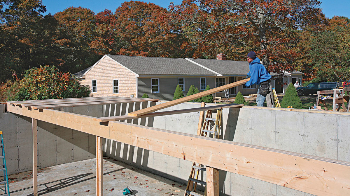 To put the joists in place, slide them over to the beam on top of its neighbor already lying flat between the mudsill and support beam
