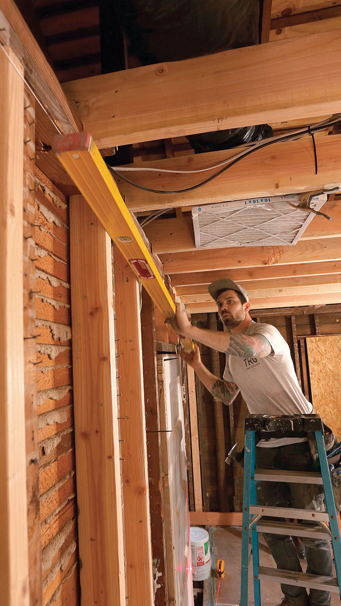 Check your work. With all the new studs tacked in place, hold a long level across the wall and check for gaps, adjusting as needed. Then remove the blocks, replace them with studs, and completely fasten each new stud in place.