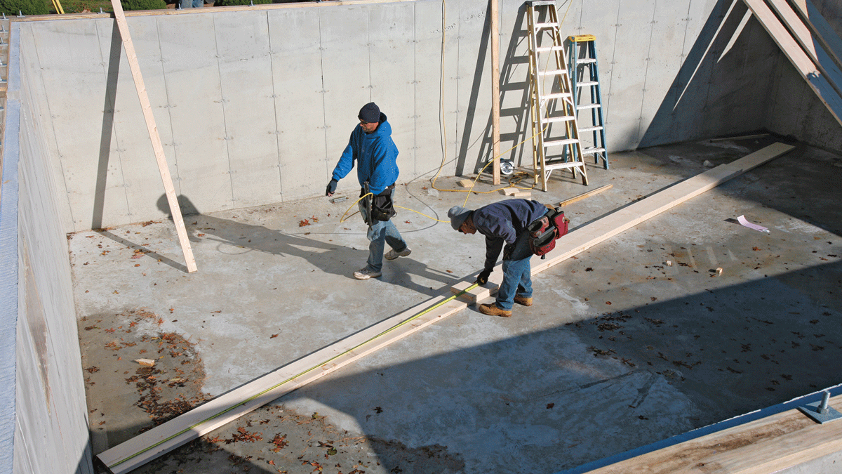 A poured concrete basement floor offers a perfect working surface for beam assembly. Double-check every layout measurement as the labeled pieces go together.