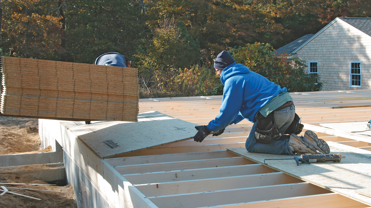 The rest of the first row of sheathing goes on in the same way as the first sheet. Nail the first course completely so the sheets will bond to the adhesive and withstand the pounding needed to get the subsequent rows into place.