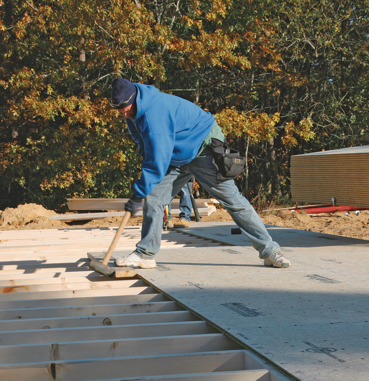 To mate the tongue and groove edges, have a helper stand on the edges as you drive the sheet into place. When working solo, hold the edges in line with one foot as you tap with the sledge hammer.