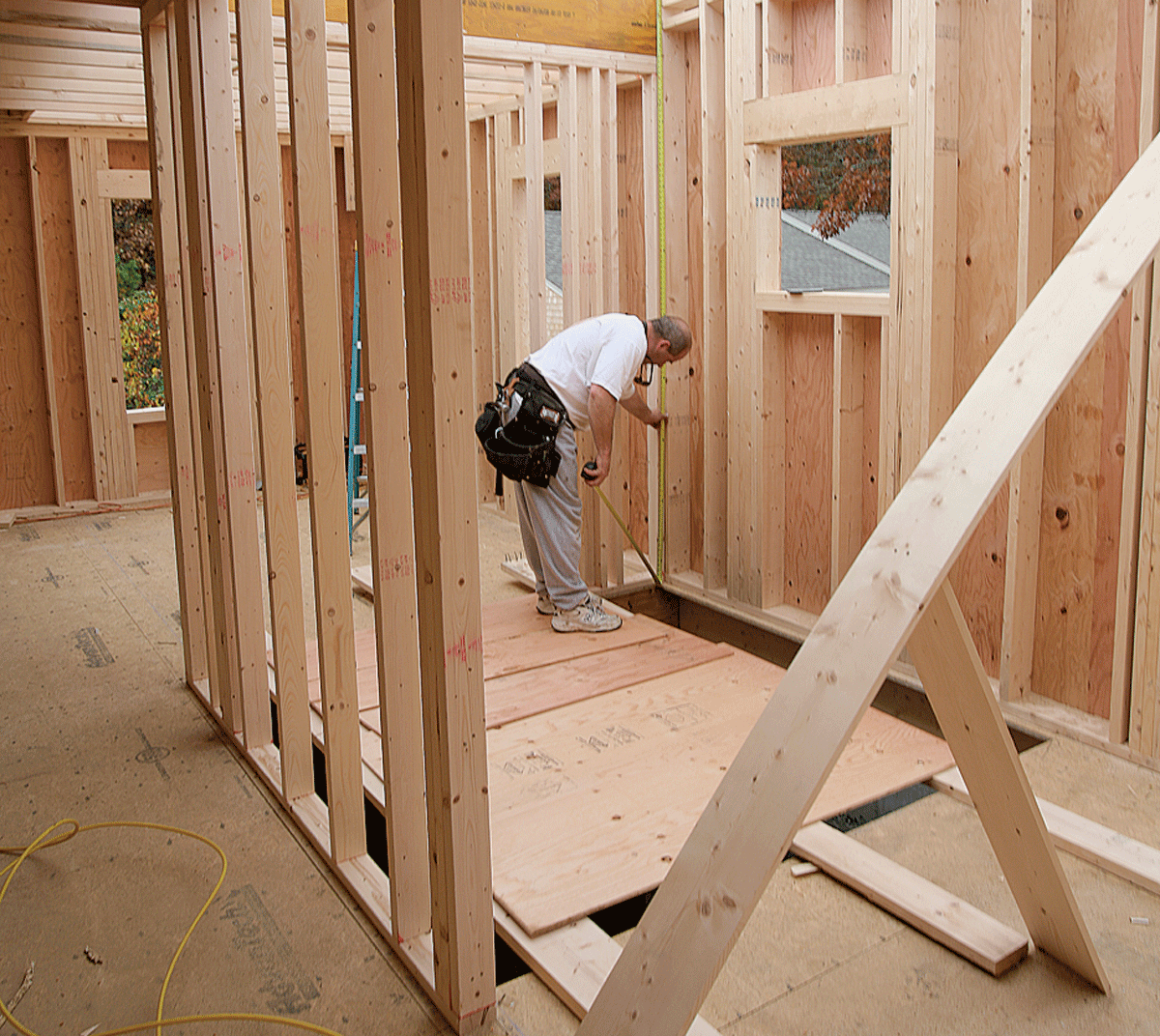 For new construction with perfectly level floors, the measurement for overall rise can be taken anywhere. Here, the measurement taken at the back of the chase also locates the height of the landing.