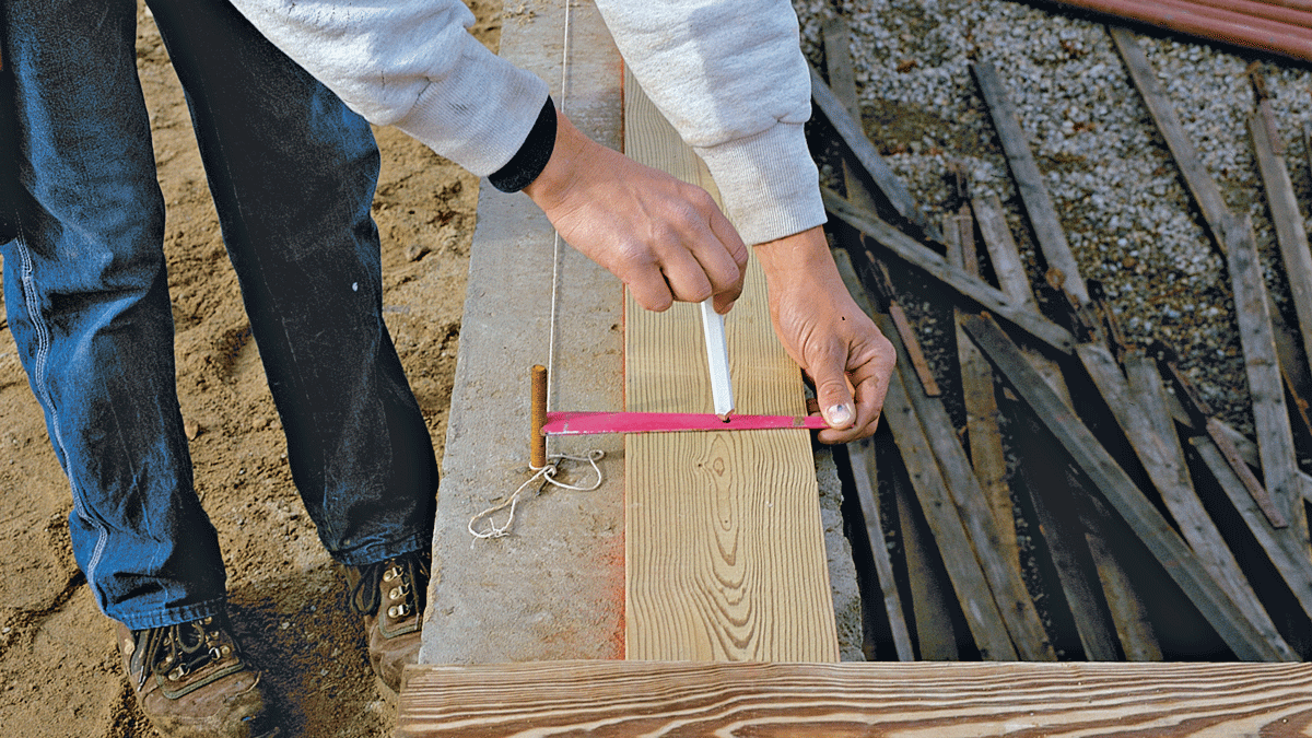 A homemade jig registers against the bolt and includes a hole for marking the bolt-hole location. This jig works best with 10-in. foundations or wider.