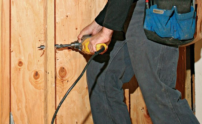 Man using a power drill rested on his thigh to make a hole in a stud to pull a cable through.
