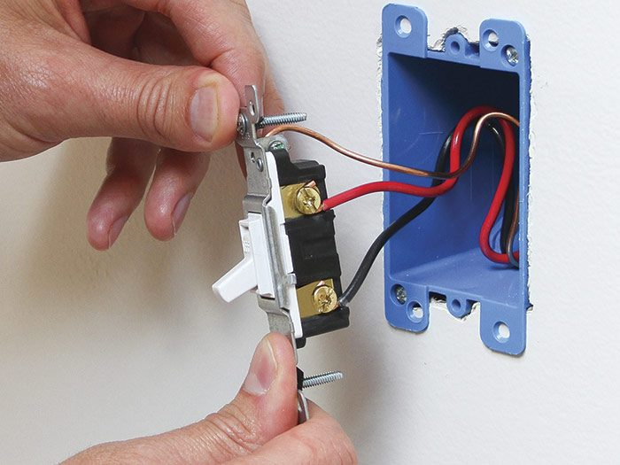 Fold the wired device into the box and secure it with mounting screws. Replace the cover plate.