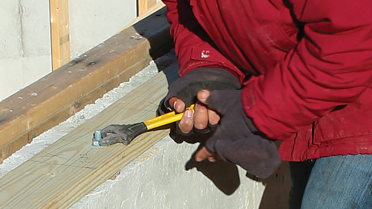 Tighten the anchor bolts. We put down a layer of foam sill gasket and transfer the anchor-bolt locations to the mudsill. Then we drill 5⁄8-in. holes to accommodate the bolts, which are capped with nuts and flat washers. We tighten the anchor bolts with an adjustable wrench until the wood fibers begin to compress.