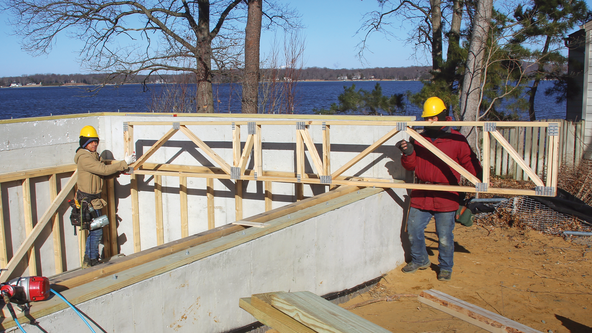 Work away from obstacles. This floor is framed within the foundation on two sides so the grade can be higher against the home in this area. We start at the first truss parallel to the foundation wall because there's more room here at the beginning of the floor framing than if we worked from the other end of the space.