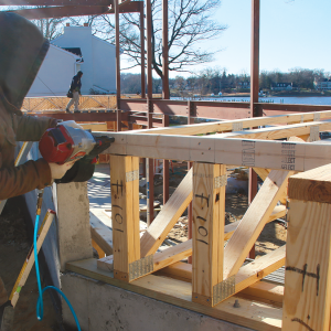 Connect the top chords. These trusses, which are flush with the foundation wall, have a 2x4 band to help plumb the trusses and strengthen the assembly. We transfer the truss layout to the band before installing it, and follow the component manufacturer's instructions for fastening.