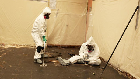 two people in hazmat suits removing asbestos floor tiles