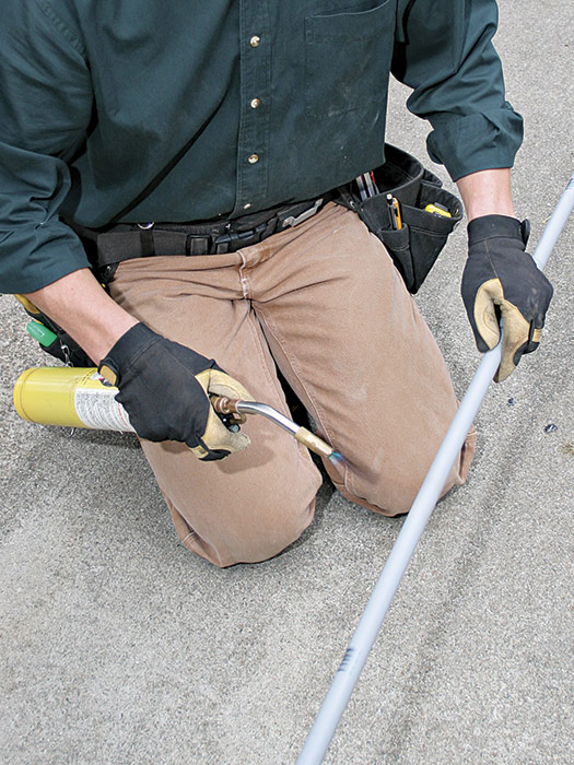 To bend PVC pipe, heat it with a handheld MAP-gas torch. Rotate the pipe and keep the torch moving to heat the pipe evenly.
