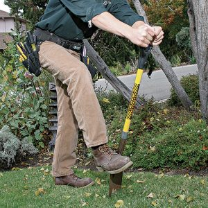 A Use a square-nosed shovel to create shallow slots so you can tuck lo-vo cable into the ground.