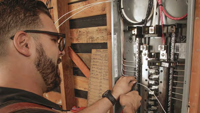 electrician wiring a circuit panel