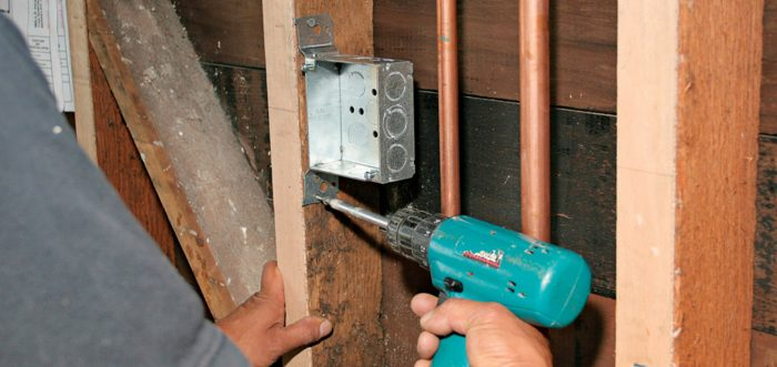 Man using a screw gun to attach a box with integral brackets to a stud.