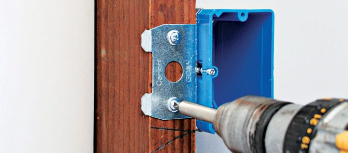 Using a screw gun to attach an adjustable box to a stud.