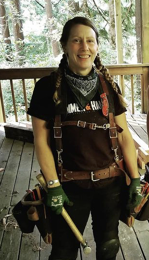Woman Carrie Healy stands on deck with her tool bag and a hammer