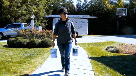 Brooke Cambridge stands with pain cans in driveway