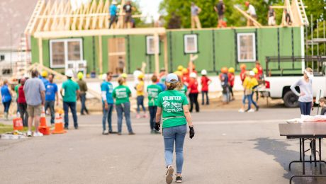 Group of volunteers gathers at a Habitat for Humanity house