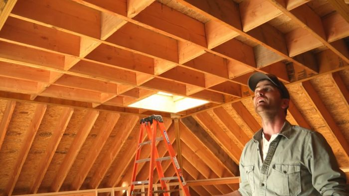 Justin stands beneath a hip roof next to a ladder