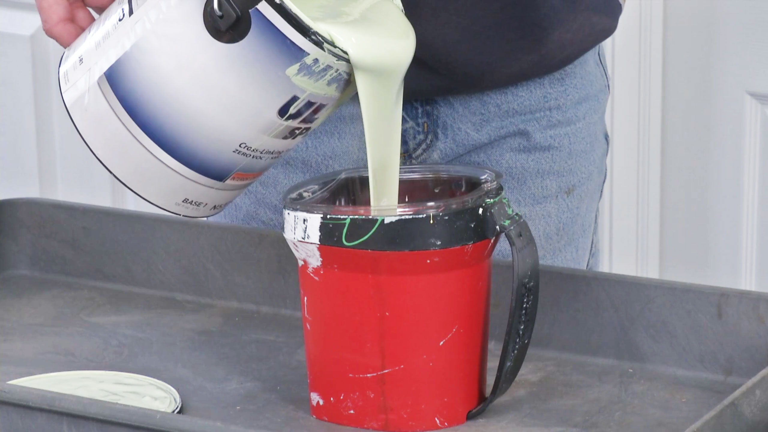 Paint is poured into red paint pail
